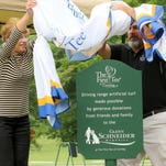 Pam Schneider, widow of Glenn Schneider, and The First Tee of Corning Director Jon Wilbur unveil a plaque commemorating the Glenn Schneider Memorial Fund driving range at Corning Country Club during a ceremony Tuesday afternoon.