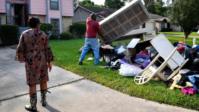 Ann Neal watches as her husband, Willie, tosses a boxspring onto the already large pile of debris on their front lawn after their home was flooded by water from Hurricane Harvey.