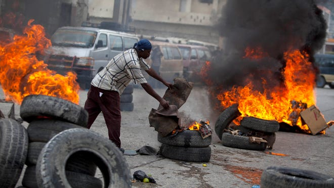 A demonstrator adds cardboard to burning tires blocking the capital's main street during a protest against the government of President Michel Martelly in Port-au-Prince, Haiti on Monday.