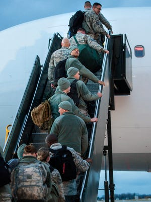 Several hundred airmen from the 158th Fighter Wing of the Vermont Air National Guard board a plane after a deployment ceremony at the air base in South Burlington on Wednesday, December 6, 2016.