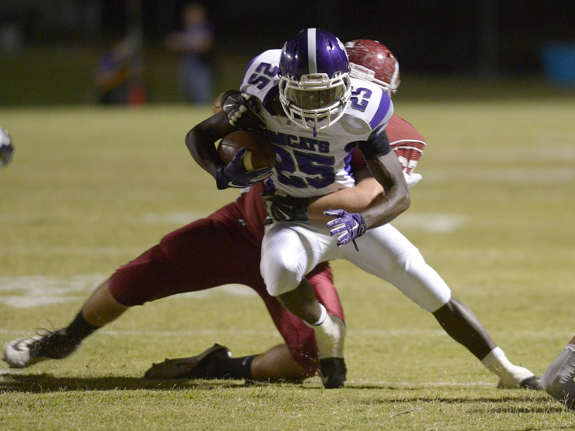 Haywood's Xavier Walker (25) is wrapped up by Crockett County's Andy Steele (67) Friday in Alamo.