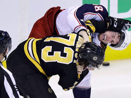 Columbus Blue Jackets center Pierre-Luc Dubois, right, hangs onto Boston Bruins defenseman Charlie McAvoy (73) as they fight during the third period of an NHL hockey game in Boston, Monday, Dec. 18, 2017. (AP Photo/Charles Krupa)