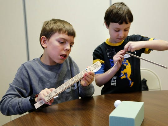 Josh Ellington, 10, left, and Josh Smith, 9, use scrap household items to construct a robotic arm during Junk Drawer Robotics Tuesday, December 2, 2014, at Kossuth Street Baptist Church. The class for 4th and 5th grade students is part of the Wildcat Creek Home Educators' Cooperative. Homeschooled students gather with other homeschooled students from 9 a.m. til noon every other Tuesday at the church for a variety of classes.