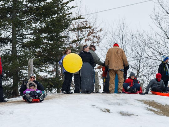 Sledders gather atop the hill during the 2016 Winterfest family event at Lisbon Community Park.