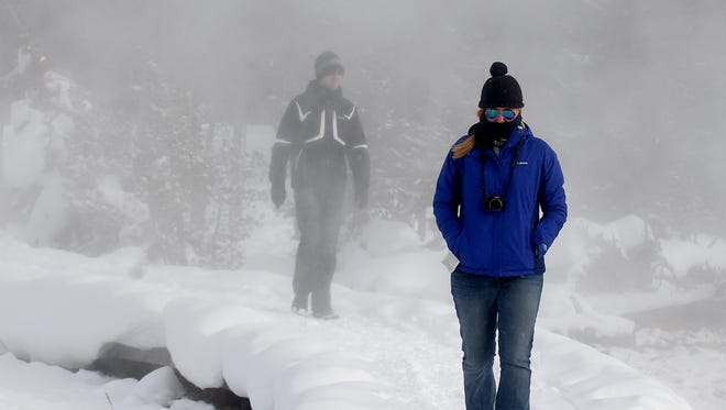 Chris Donnelly, left, of Perth, Australia, and Kate Fitzgerald of Sydney, Australia, check out Black Sand Basin along a boardwalk at Yellowstone National Park on Jan. 15.