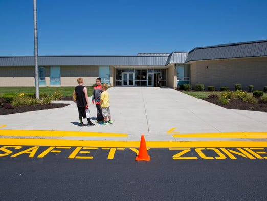 Mintonye Elementary students Carter Norsworthy, left, Jacob Newman and James Hunt talks outside during their first day back at the school Wednesday, August 13, 2014, near Romney. After a tornado struck the school on Nov. 17, 2013, students and staff were excited to be back.