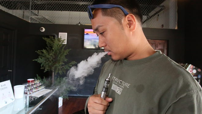 Customer Noel Catacutan uses his own vape pen as he looks over the vaping pens at the Flash Vapor e-cigarette store in West Nyack on April 24, 2014.