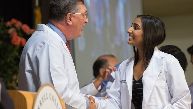 Pravleen Bains, right, shakes hands with Dr. Oliver Hayes, senior associate dean of Graduate Medical Education, left, during the Burrell College of Osteopathic Medicine Class of 2022 White Coat Ceremony, Friday August 10, 2018 at the Las Cruces Convention Center.