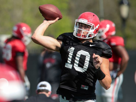FILe - In this March 28, 2017, file photo, Georgia quarterback Jacob Eason (10) throws during spring NCAA college practice in Athens, Ga. Though Eason and the Bulldogs fell short of 2016 expectations, coach Kirby Smart is seeing Eason's added maturity make a difference in his second spring practice. (John Roark/Athens Banner-Herald via AP, File)