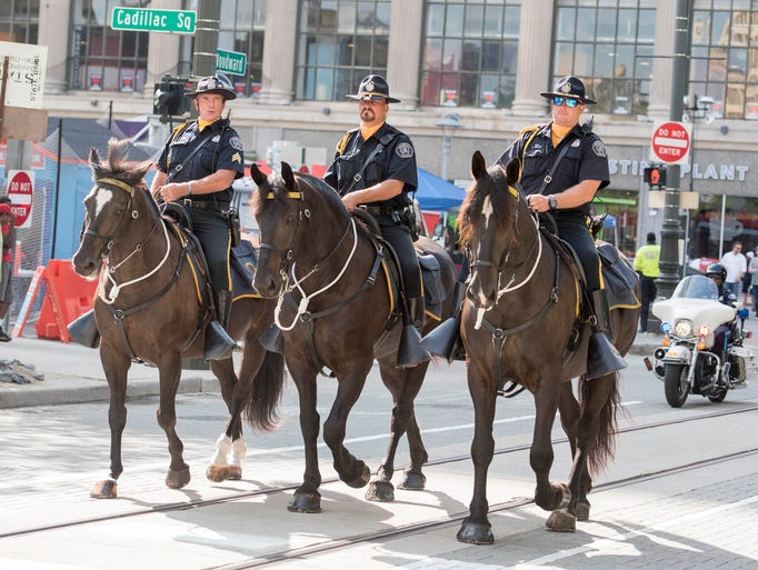 Detroit mounted police officers ride down Woodward