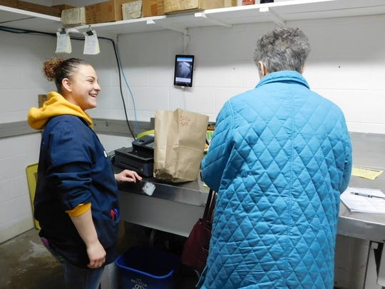 Sam Menkhoff, left, a Hasselbach Meats clerk, serves a customer in the small freezer meat pickup room. The store remains open during the remodeling project, but customers must write up an order for staff to fill while they wait.