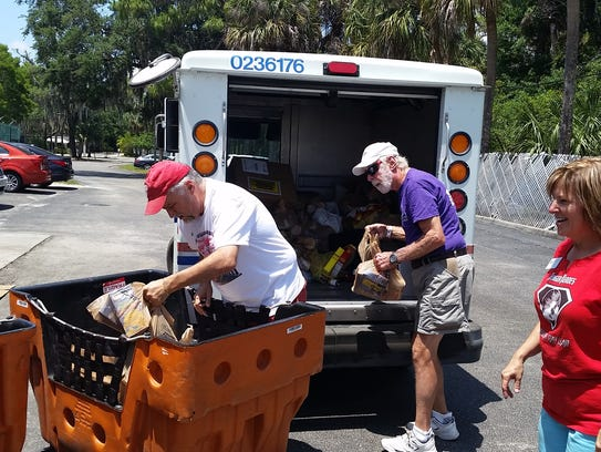Volunteers empty food from letter carriers vehicles