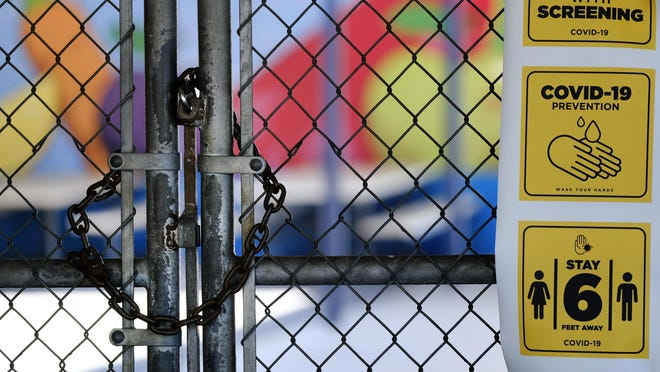 A chain-link fence lock is seen on a gate at a closed Ranchito Elementary School in the San Fernando Valley section of Los Angeles on Monday. Amid spiking coronavirus cases, Los Angeles Unified School District campuses will remain closed when classes resume in August.