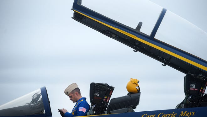Blue Angels No. 7 pilot Capt. Jeff Kuss checks his cell phone after landing at Wallops Flight Facility on Tuesday, Dec. 2, 2014. Capt. Kuss and Capt. Corrie Mays flew into Wallops for a preflight survey of the facilities at Wallops and at Ocean City, Md. for the upcoming Ocean City Air Show in June.