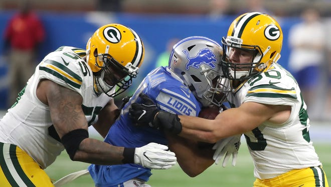 Green Bay Packers outside linebacker Ahmad Brooks (55) and inside linebacker Blake Martinez (50) sandwich Detroit Lions running back Ameer Abdullah (21) on Dec. 31, 2017, at Ford Field in Detroit.