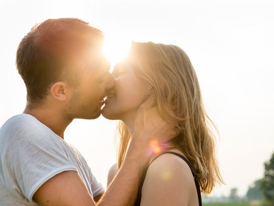 summer portrait of a kissing young adult couple, back lit