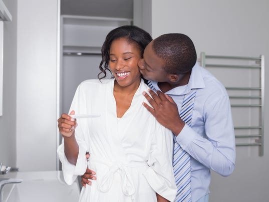 Excited couple looking at positive pregnancy test