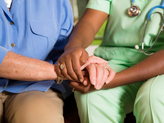 Home healthcare nurse holds senior woman's hands. Consoling. Kindness.