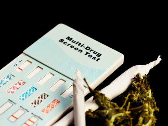 Home drug test kit next to reefers and raw marijuana