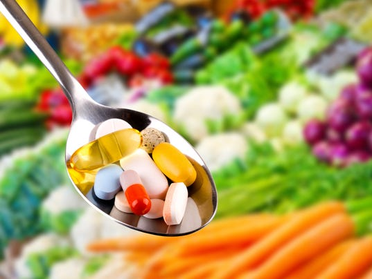 Spoon with pills, dietary supplement on vegetable background