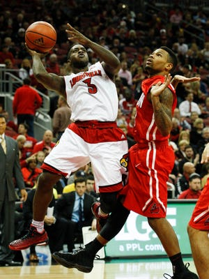 U of L's Chris Jones, #3, changes his shot against Cal State Northridge's Taelin Webb, #0, during their game at the KFC Yum! Center.