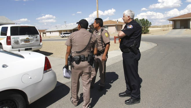 Navajo Nation police Officer Jonathan Johnson, right, speaks with Shiprock Police Lt. Phillip Joe and  Farmington Police Chief Steve Hebbe Aug. 7, 2014, during an investigation in a housing area in Ojo Amarillo.
