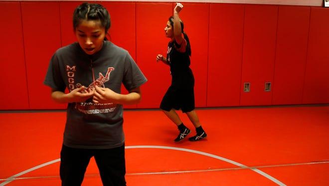 Shiprock wrestlers Chasitty Todacheenie, left, and Zhoniba Belone warm up on Monday before wrestling practice at Shiprock High School.