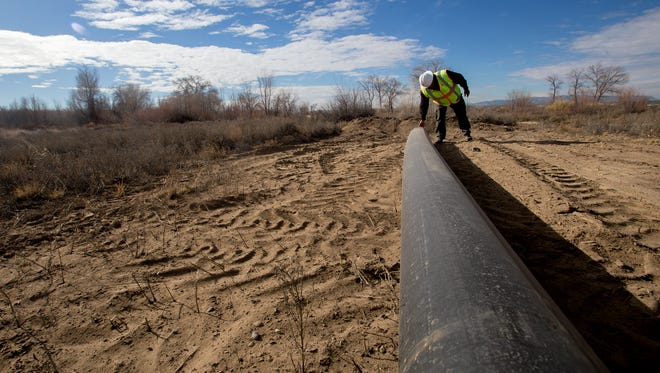 Gregory Bahe, operations supervisor for water and wastewater in the engineering, construction and operations division at Navajo Tribal Utility Authority, inspects a pipe on Dec. 21 that will be used to repair a ruptured pipeline in Shiprock