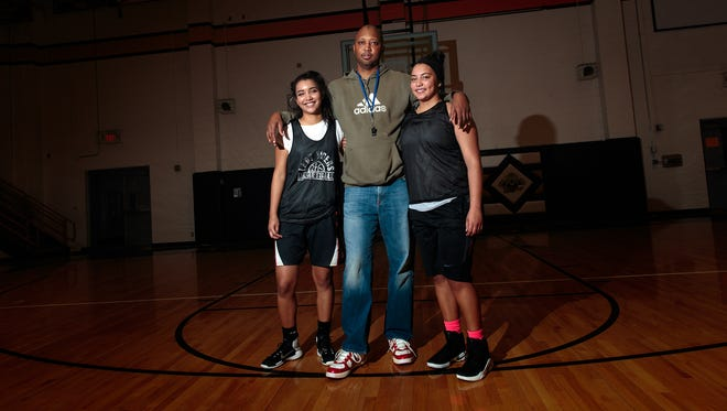 Aztec High School girls basketball head coach Robert McCaskill poses for a portrait with his daughters, Myra McCaskill, left, and Makayla McCaskill during basketball practice on Thursday at Lillywhite Gym in Aztec.