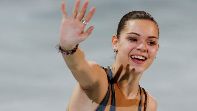 Adelina Sotnikova (RUS) waves to the crowd in the flower ceremony for the women's free skate program.