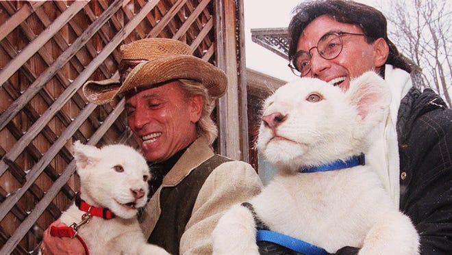 Entertainers Siegfried and Roy hold Future (left) and Sunshine, the two male white lion cubs they donated to the Cincinnati Zoo in 1998.