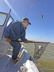 Gene Talamantes shares in the netting duties during a windy day on Baffin Bay and beyond.