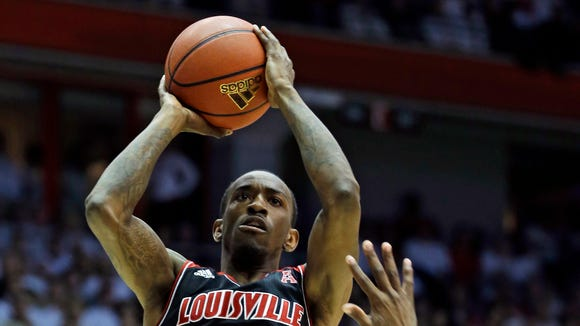 Louisville guard Russ Smith (2) shoots over Cincinnati guard Sean Kilpatrick in the second half of an NCAA college basketball game, Saturday, Feb. 22, 2014, in Cincinnati. Smith scored 10 points in the game won by Louisville 58-57. (AP Photo/Al Behrman)