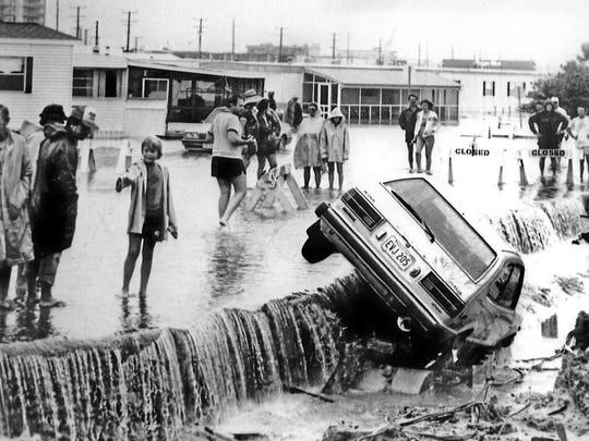 Spectators look at a car washed off Sinepuxtent Avenue as a result of flooding by Hurricane Gloria on Sept. 27, 1985. The hurricane destroyed much of the Boardwalk and flooded the resort. It also prompted creation of the Beach Replenishment Project which widened the beachfront to 200 feet from the Inlet to Fenwick Island. A seawall from Fourth Street to 27th Street was also constructed.