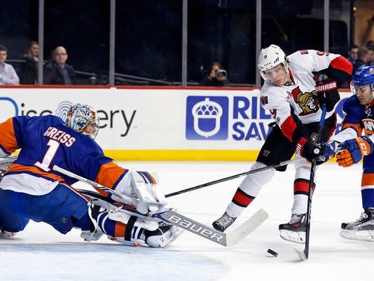 Ottawa Senators right wing Bobby Ryan (9) is tripped by New York Islanders defenseman Adam Pelech (50) as he looks to shoot around Islanders goalie Thomas Greiss (1) in the first period of an NHL hockey game, Sunday, April 9, 2017, in New York. (AP Photo/Adam Hunger)