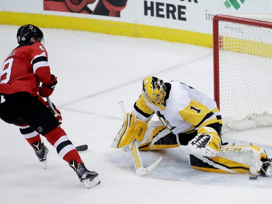Pittsburgh Penguins goaltender Casey DeSmith (1) blocks a shot by New Jersey Devils left wing Taylor Hall (9) during the third period of an NHL hockey game Saturday, Feb. 3, 2018, in Newark, N.J. The Devils won 3-1. (AP Photo/Julio Cortez)