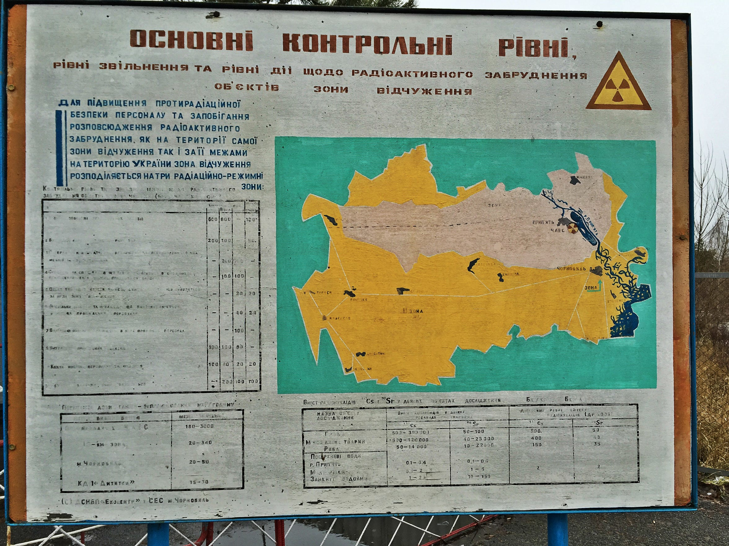 A faded sign with information about radiation levels marks the entrance to the Chernobyl Exclusion Zone in Ukraine.
