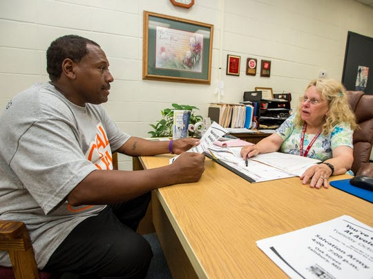Melanie Carey, social services case worker at the Salvation Army in Salisbury, meets with Robert Banks in her office. The middle class is shrinking in Delmarva as the income gap grows along with the rest of the nation. Carey's days are filled with clients struggling to make ends meet.