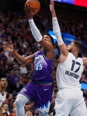 Utah Jazz guard Donovan Mitchell (45) lays the ball in past Memphis Grizzlies center Jonas Valanciunas (17) during the first half of an NBA basketball gam  Saturday, Dec. 7, 2019, in Salt Lake City. (AP Photo/George Frey)