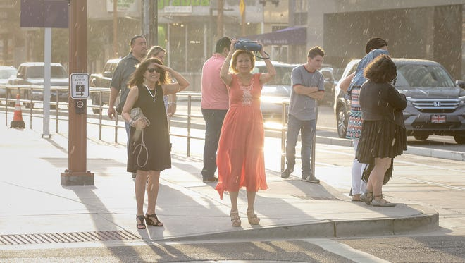 Pedestrians in downtown Phoenix cover their heads to avoid light rain on Aug. 16, 2016
