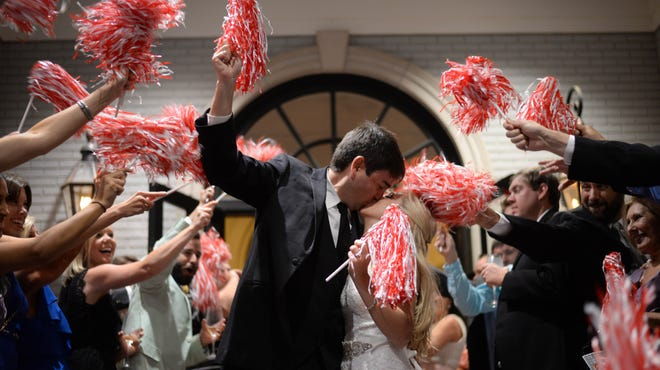 Wedding guests shake red-and-white pom-poms as University of Alabama graduates Courtney and Scott Jenkins leave their wedding reception in Vestavia Hills, Ala., on Aug. 9, 2014. Like many other couples in states where college football is popular, the Jenkinses incorporated a football theme and scheduled their wedding outside of football season to avoid the dilemma of planning around the game schedule.