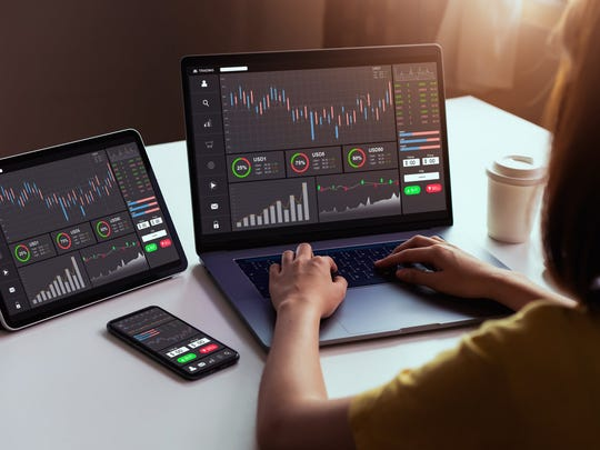 a stock trader uses a laptop, a ipad and a smartphone to monitor statistics