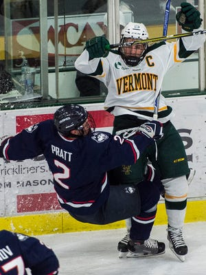 UVM's Rob Darrar lays out UConn's Johnny Austin during their Hockey East men's hockey match up at Gutterson Fieldhouse Tuesday night, Nov. 21, 2017.