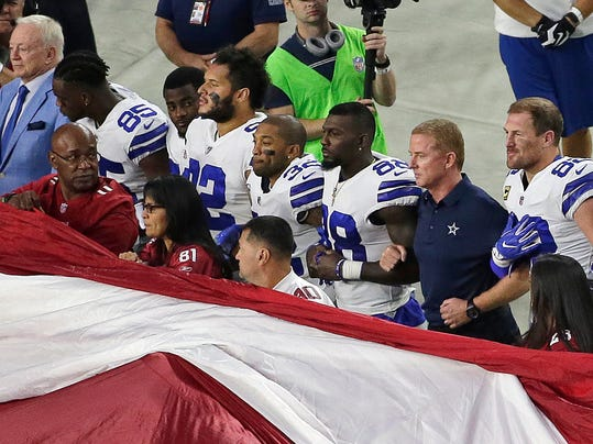 FILE - In this Sept. 25, 2017, file photo, Dallas Cowboys owner Jerry Jones, left, and head coach Jason Garrett, second from right, stand with their players for the national anthem prior to an NFL football game against the Arizona Cardinals in Glendale, Ariz. The Cowboys already have as many losses as last year's NFC East champ, they're dogged by anthem questions because of their outspoken owner and their defense looks eerily similar to the lost season of 2015. The bye wasn't offering much of a break from the mental grind of the season. (AP Photo/Matt York, File)