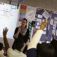 This April 24, 2013, photo shows Lauren DuLac teaching her fifth-grade class math at Detroit Merit Charter Academy in Detroit.