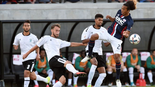 Rochester Rhinos defender Joseph Farrell (15) kicks the ball away from New England Revolution midfielder Zachary Herivaux (21) during the first half at Providence College.