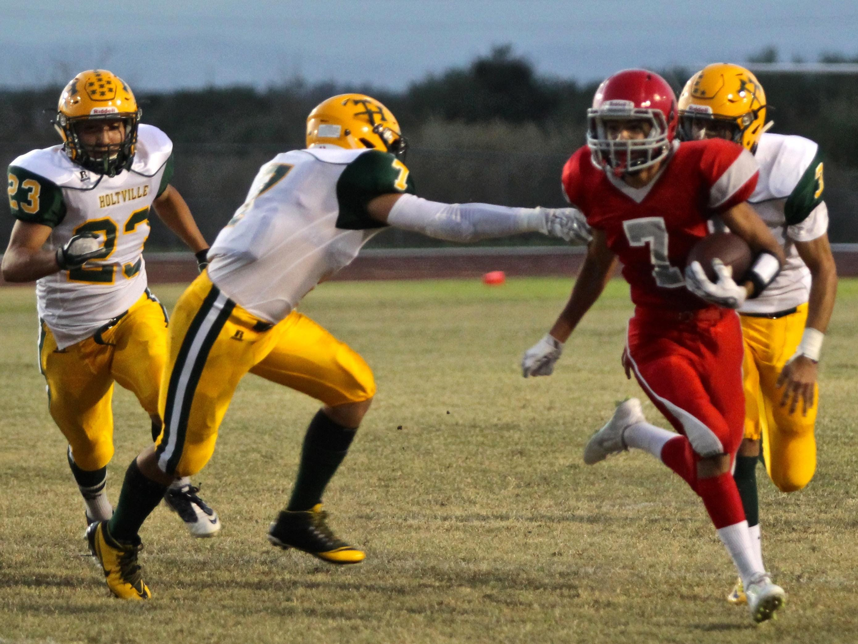 Desert Mirage's Jesus Ortiz (7) sprints as he attempts to avoid being tackled by Holtville's Adam Montes (7) in high school football Friday night.