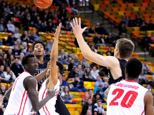 Utah State's Chris Smith makes a pass over two New Mexico players to teammate Quinn Taylor during an NCAA college basketball game, Tuesday, Feb. 9, 2016, in Logan, Utah. (John Zsiray/The Herald Journal via AP) MANDATORY CREDIT