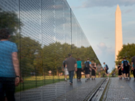 Visitors to the Vietnam Veterans Memorial are reflected
