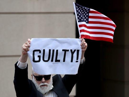 'Culpable' dice el letrero que sostiene este manifestante